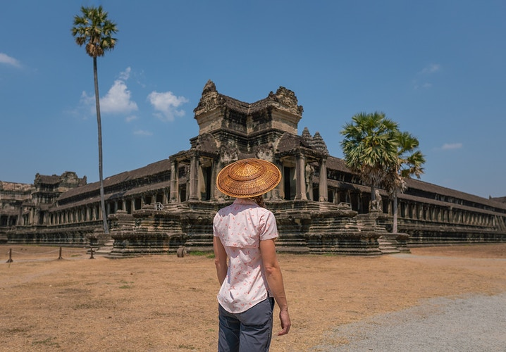 A woman wearing a traditional hat in front of Angkor Wat, Siem Reap Cambodia - Daniel John Photography