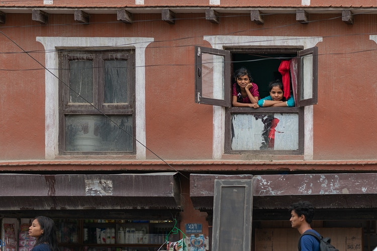 Two young girls staring at the camera over a crowded street in Kathmandu Nepal - Daniel John Photography