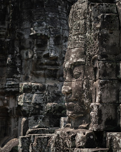 Two faces carved into stone at Bayon Temple in Siem Reap, Cambodia - Daniel John Photography