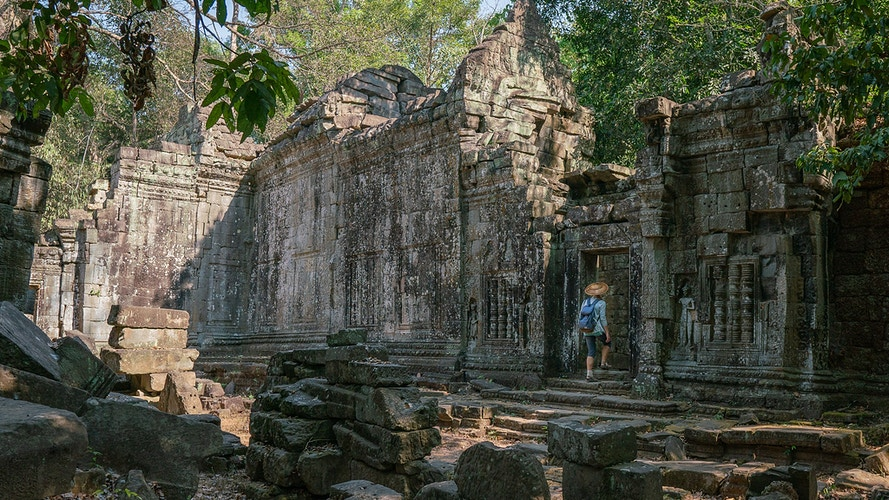 A woman walking through a doorway in ancient ruins in Siem Reap Cambodia - Daniel John Photography