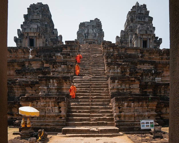 Three buddhist monks descending large steps at a temple in Siem Reap, Cambodia - Daniel John Photography