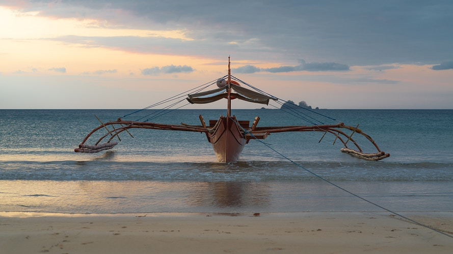 A beached bangka bamboo boat on a beach in the Philippines - Daniel John Photography
