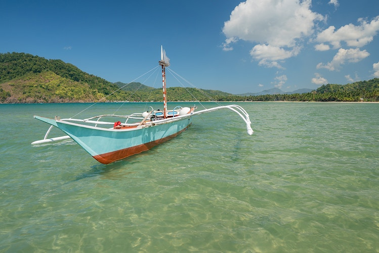 A bangka boat in a bay in the Philippines - Daniel John Photography