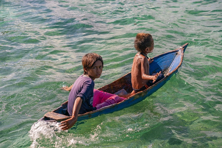 Two young children paddling a dugout canoe on Mabul Island in Sabah, Malaysia, Borneo - Daniel John Photography