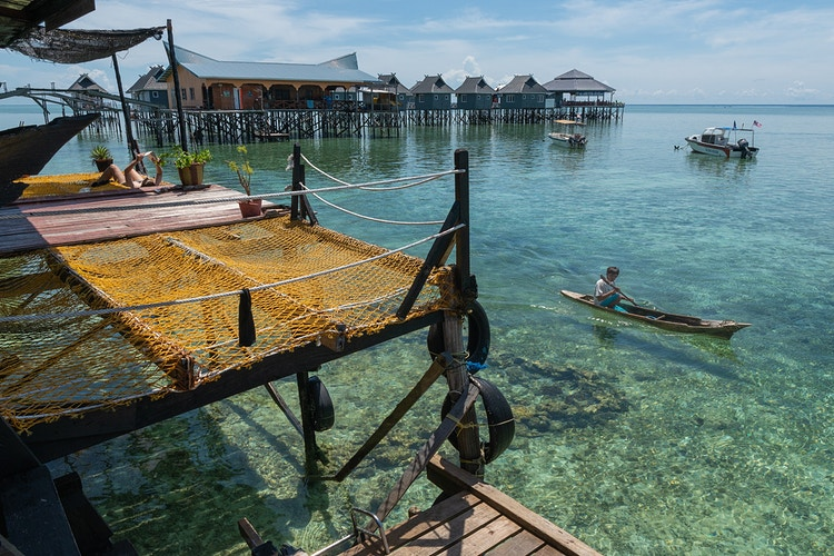 A man paddling a dugout canoe while a woman relaxes reading a book on a house on stilts in Mabul, Malaysia - Semporna, Sabah, Borneo - Daniel John Photography