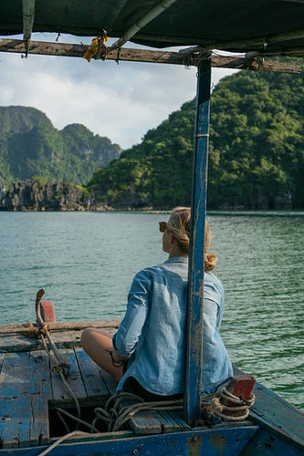 A woman sitting at the front of a boat in Halong Bay, Vietnam - Daniel John Photography