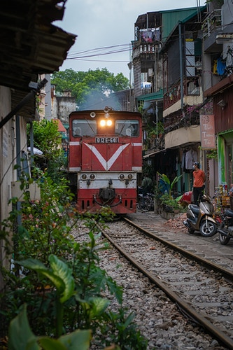A train moving down a narrow alleyway in Hanoi Vietnam - Daniel John Photography