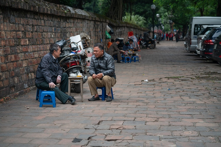 Two men talking and enjoying tea on tiny chairs in Hanoi Vietnam - Daniel John Photography