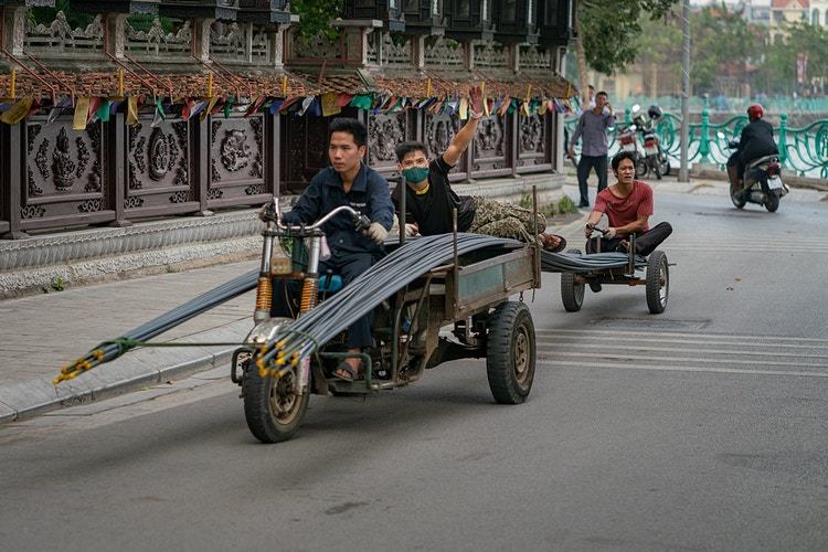 Three Vietnamese men transporting steel rods on a makeshift vehicle in Hanoi Vietnam - Daniel John Photography