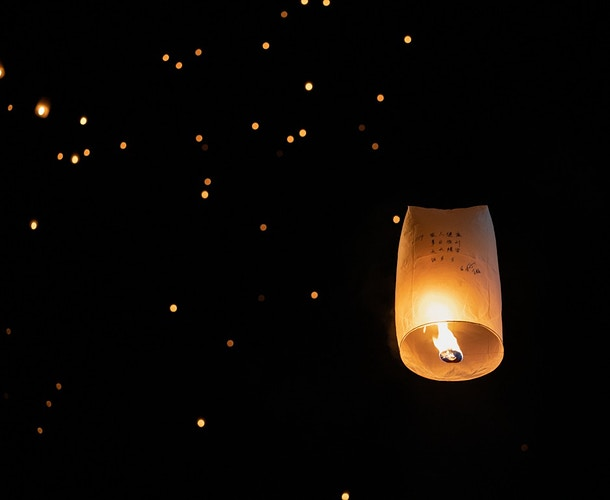 A lantern in front of dozens of laterns launched at New Year's Eve at Chiang Mai Thailand - Daniel John Photography
