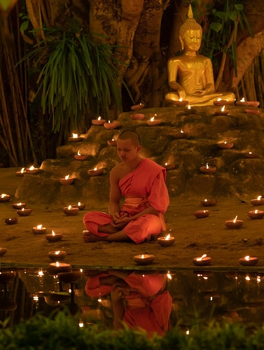 A buddhist monk praying at a temple at New Year's Eve in Chiang Mai, Thailand - Daniel John Photography