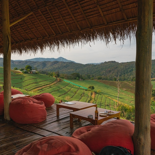 A bar/restaurant with bean bag chairs overlooking rice paddies in Pai Thailand - Daniel John Photography