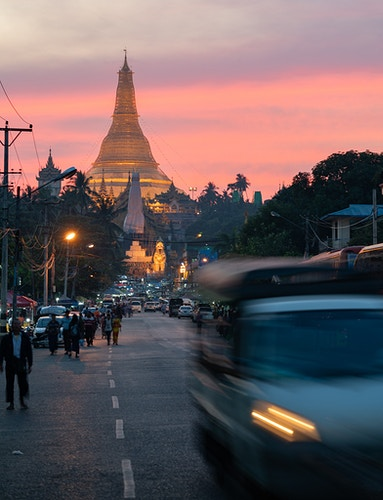 Shwedagon Pagoda in Yangon, Myanmar with a colorful sunset, pedestrians, and traffic - Daniel John Photography