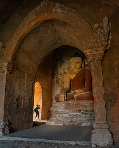 A woman photographing a large Buddhist statue in a temple in Bagan, Myanmar - Daniel John Photography