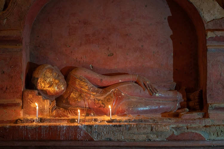 A resting Buddha statue with lit candles in Bagan Myanmar - Daniel John Photography