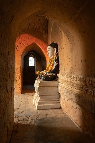 A Buddha statue with spiraling light in a temple in Bagan Myanmar - Daniel John Photography