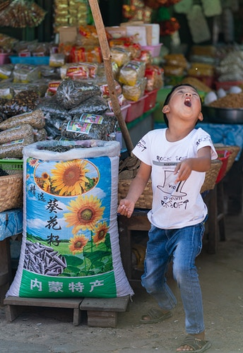 A young boy tossing a sunflower seed in the air in Inle Lake Myanmar (he missed) - Daniel John Photography