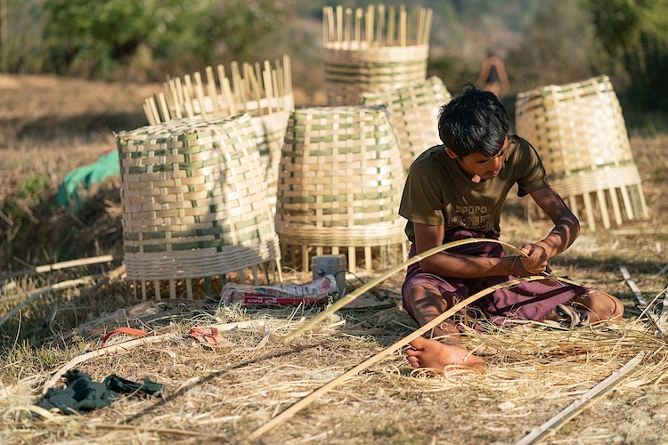 A man cutting bamboo in preparation to make baskets in Myanmar - Daniel John Photography