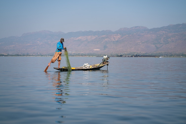 A man laying out a net on Inle Lake in Myanmar - Daniel John Photography