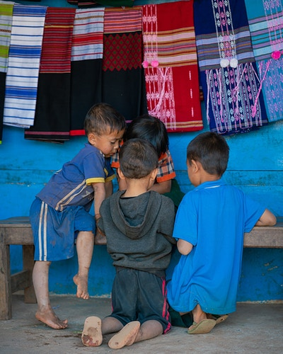 Four young boys crowded around an object in front of hand-made scarves in Loikaw Myanmar - Daniel John Photography