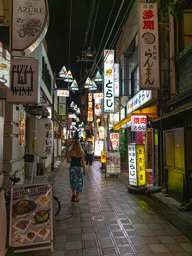 A woman walking down a small street with neon signs in Nakano, Tokyo, Japan - Daniel John Photography