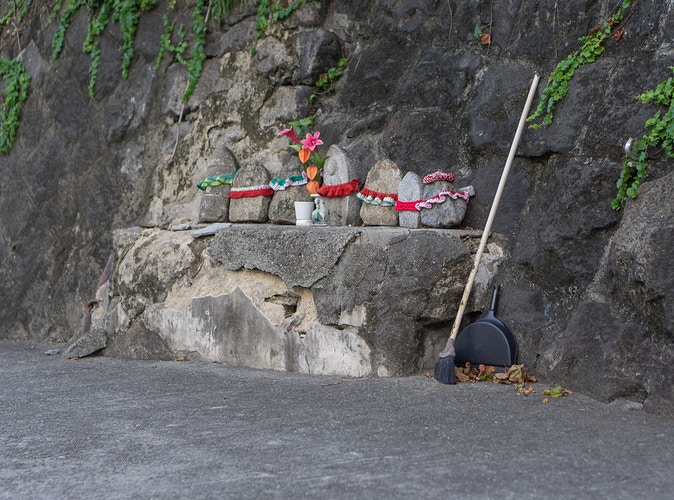 A small clean shrine on a sidewalk in Onomichi Japan next to a broom, dustpan, and pile of refuse - Daniel John Photography