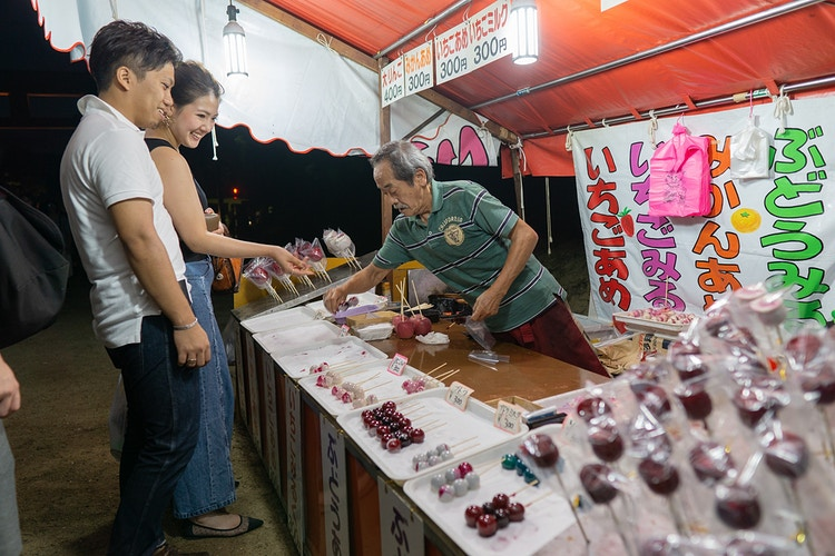 Two people choosing a confectionary at a stall as a vendor packages candy in Nara, Japan - Daniel John Photography