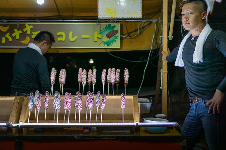 A vendor with visible neck tattoos in front of chocolate-covered bananas in Nara, Japan - Daniel John Photography