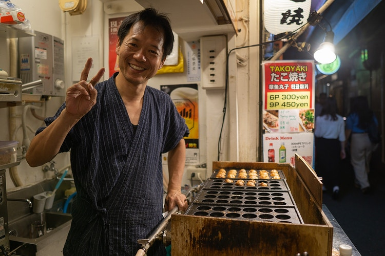 A japanese street vendor in his tiny stall selling takoyaki in Osaka Japan - Daniel John Photography