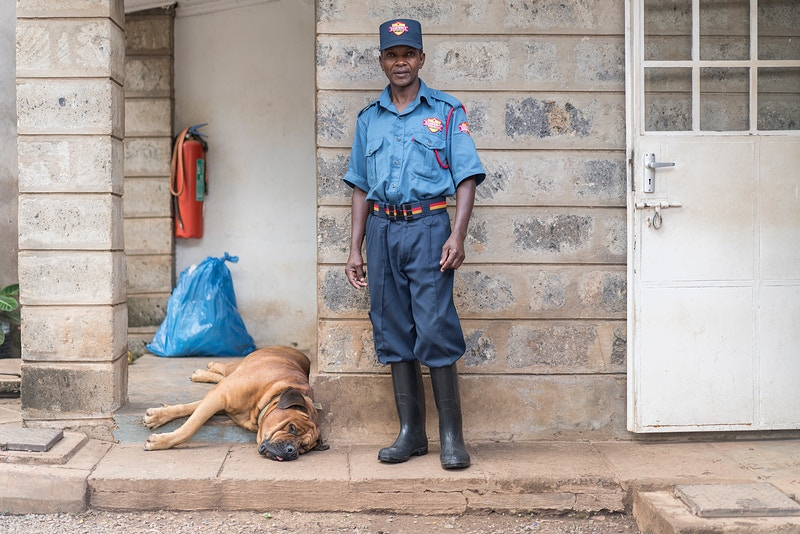 PATRICK AND HIS TRUSTY GUARD DOG PAUL. NAIROBI - GRAHAM GUY BARRATT