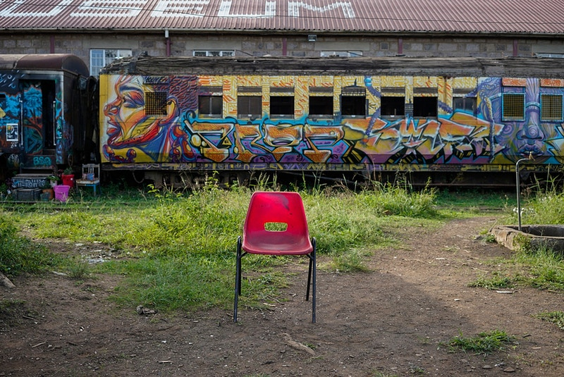 ARTISTS RED CHAIR IN THE TRAIN YARD. NAIROBI. - GRAHAM GUY BARRATT