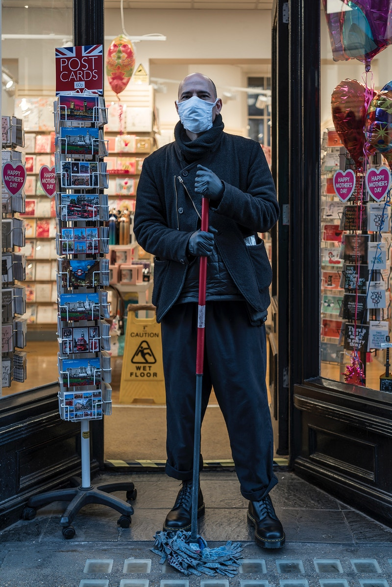ROBERT. CLEANING THE CARD SHOPS DOORSTEP AT THE END OF MOTHERS DAY, CHARING CROSS ROAD LONDON DURING THE EARLY DAYS OF THE GREAT GLOBAL PANDEMIC ARRIVING IN THE UK - GRAHAM GUY BARRATT