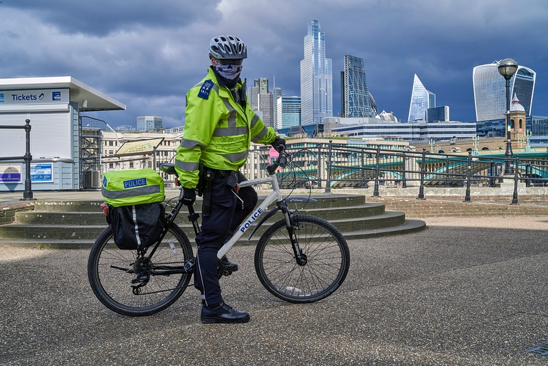 POLICE CYCLE PATROL WITH NOT SO STANDARD PANDEMIC SKULL FACE MASK. BLACKFRIARS PIER NEAR SOUTHWARK BRIDGE WITH THE CITY BEYOND MONDAY 30TH MARCH 15.48 DURING THE GREAT GLOBAL PANDEMIC OF 2020 - GRAHAM GUY BARRATT