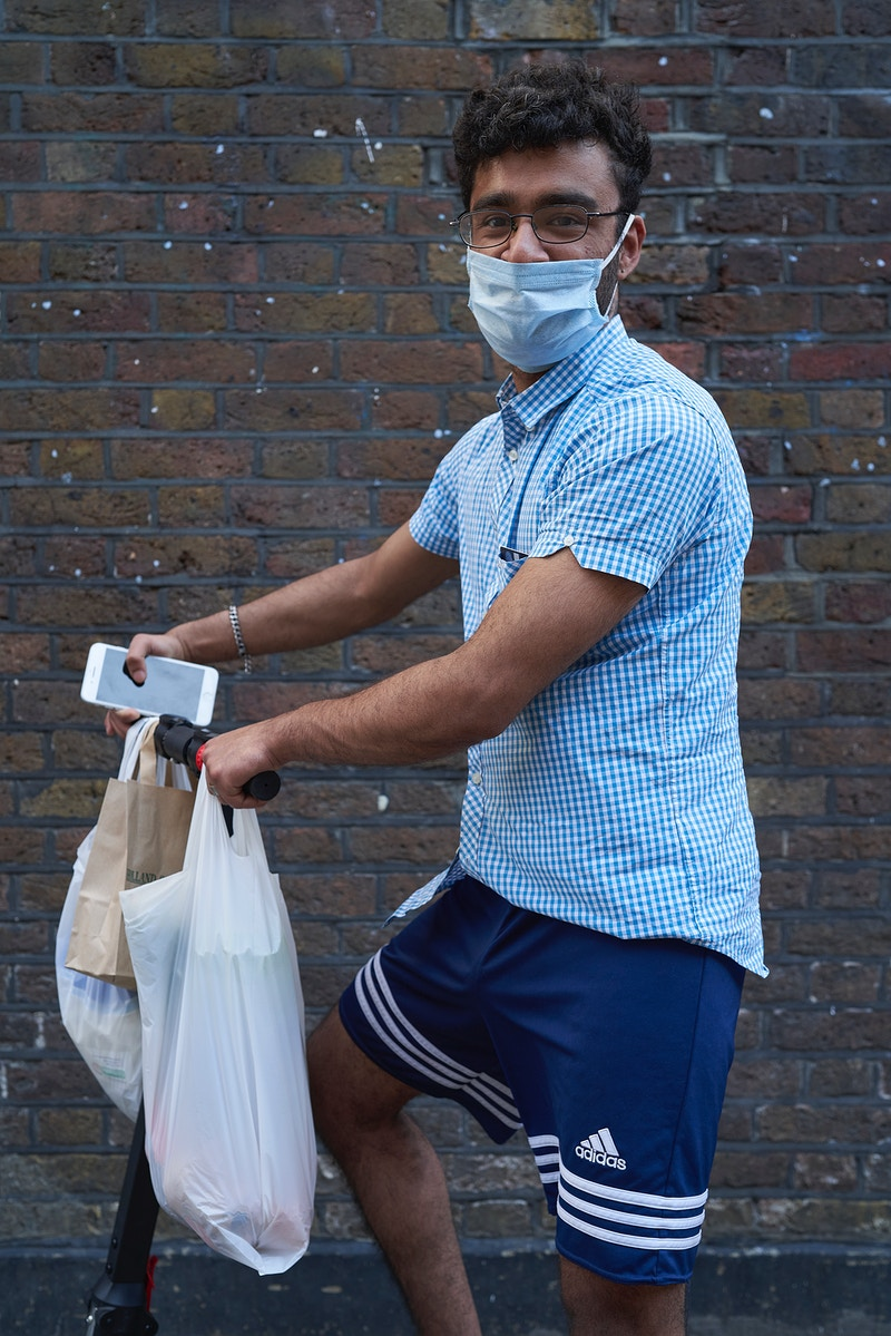 NORMAN. PROPERTY ENTREPRENEUR SCOOTERING HOME FROM COLLECTING THE GROCERIES NEAR THE TRUMAN BREWERY BRICK LANE LONDON SUNDAY 05TH APRIL 16.16 DURING THE GREAT GLOBAL PANDEMIC OF 2020 - GRAHAM GUY BARRATT