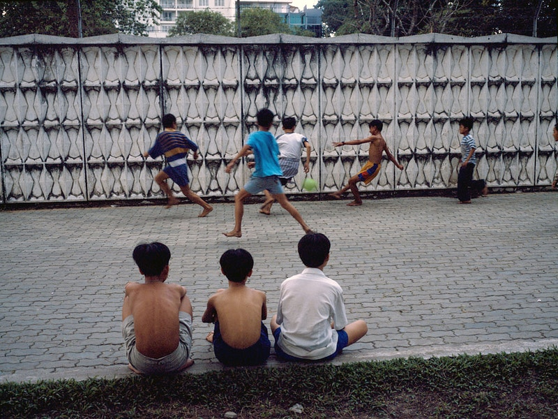 MATCH OF TODAY – FOOTBALL GAME BESIDE THE WALL OF THE FORMER U.S.EMBASSY (1965-75) ON LE DUAN BOULEVARD HO CHI MINH CITY (SAIGON) - GRAHAM GUY BARRATT