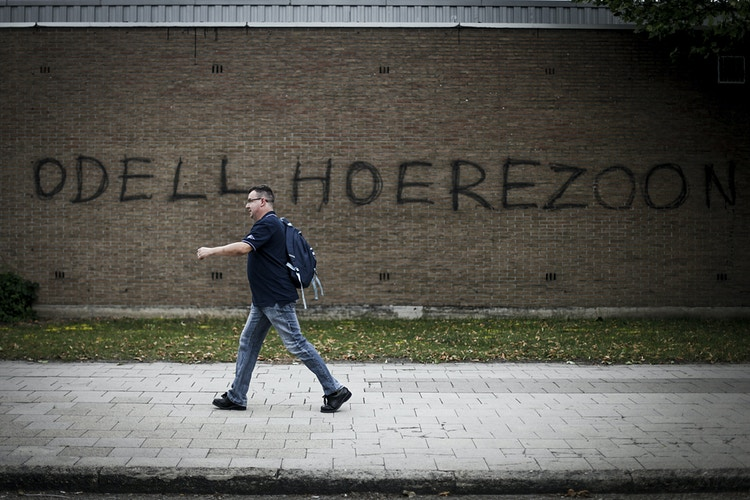 A worker passes in front of a graffiti that says: