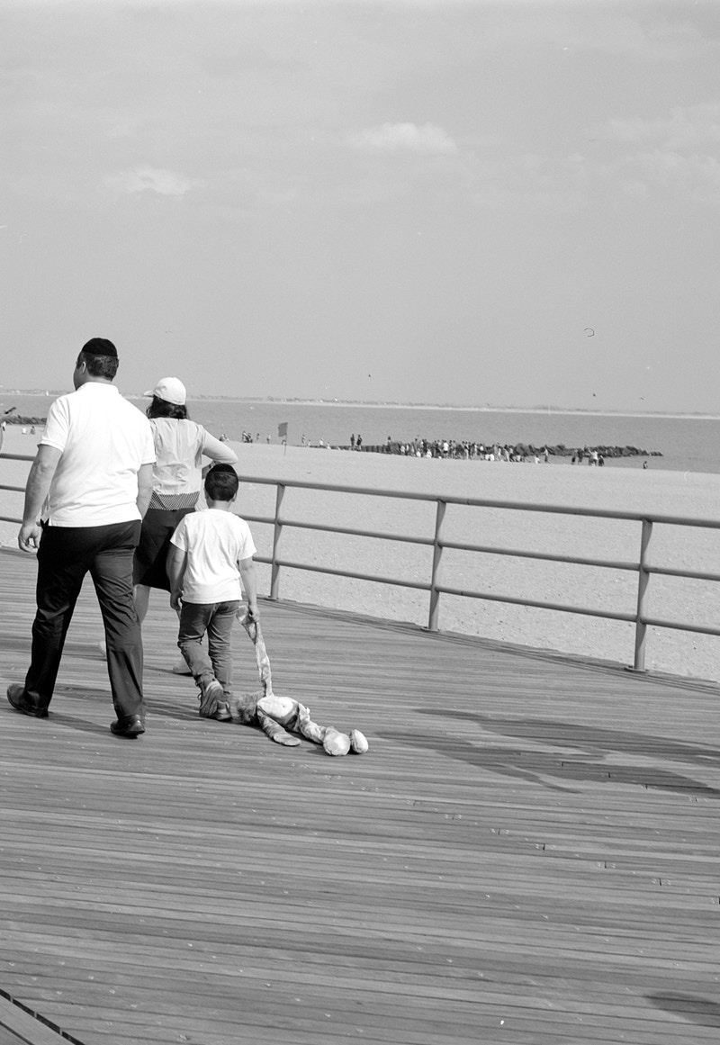 boardwalk kid drags a stuffed animal behind him - Victor Cohen